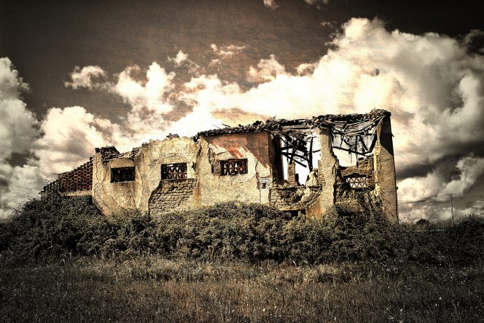A decrepit and crumbling house in a field over layed with an aged-looking photofilter